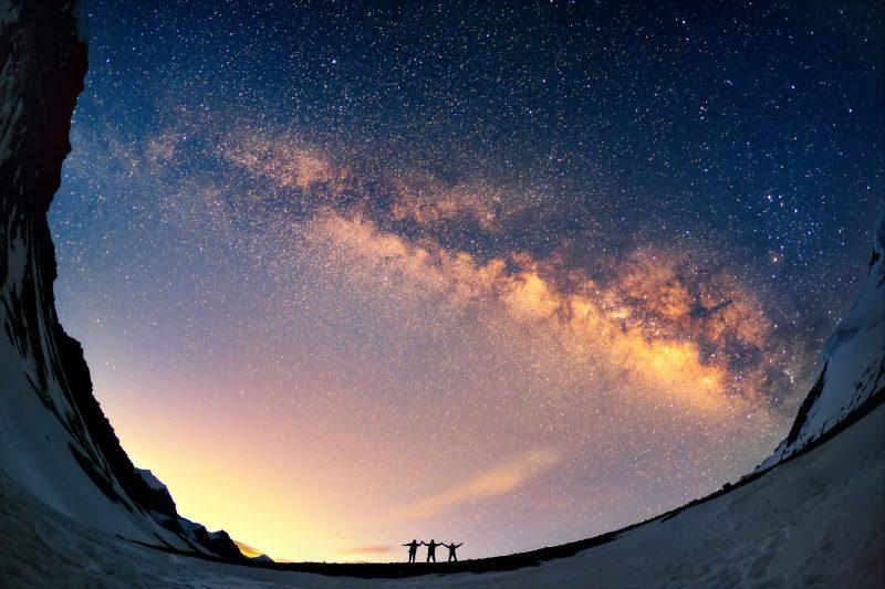Люди, держась за руки, смотрят на Млечный Путь в горах